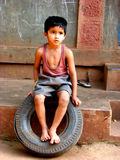Tyre Boy. An Indian boy from a village sitting on a tyre Stock Image