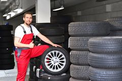 Tyre change on the car in a workshop by a mechanic. Portraits in the tyre warehouse royalty free stock images