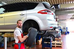 Tyre change on the car in a workshop by a mechanic. Portrait of repairmen with tire royalty free stock photography