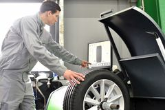 Tyre change in a garage - assembler balancing a tyre on the mach. Ine stock photography