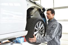 Tyre change in a workshop - assembler in working clothes. Closeup royalty free stock photography