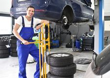 Tyre change in a workshop - portrait mechanic with stack of tyre. S for replacement Royalty Free Stock Photo