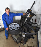 Tyre changing machine, mechanic fixing tire in car service Stock Photography