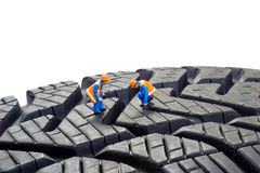 Tyre Check. Miniature workers checking the depth tread on a car tyre Royalty Free Stock Photos
