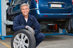 Tyre Dealer Holding A Tire Stock Image