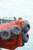 Tyre fender on tugbooat. Rubber tyre fender on blue tugbooat hul Stock Images
