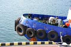 Tyre fender on tugbooat. Rubber tyre fender on blue tugbooat hul Royalty Free Stock Photo