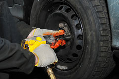 Tyre fitting with air compressed wrench Royalty Free Stock Photo