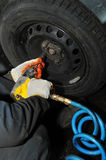 Tyre fitting with air compressed wrench Stock Photo