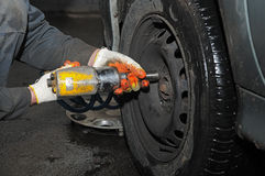 Tyre fitting repair with air compressed wrench Royalty Free Stock Photography