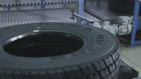 Tyre with Logo Transported by Conveyor Slow Motion. KAZAN, TATARSTAN/RUSSIA - SEPTEMBER 12 2017: Slow motion modern finished truck tyre with logo on side stock footage