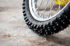 Tyre of motocross bike. On ice and snow on background, selective focus on the middle part stock photos