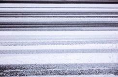 Tyre prints in wet snow on asphalt Royalty Free Stock Image