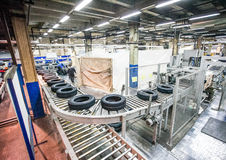 Tyre production conveyor at bright new factory. With workman Stock Image