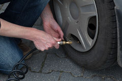 Tyre pumping. A man pumping a flat tyre Royalty Free Stock Photo