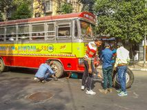 Tyre puncture on a busy road. Kolkata, West Bengal, India- December 17, 2017: A bus tyre puncture was held on a busy road and then a group of labor try to Royalty Free Stock Photo