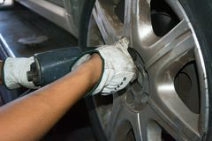 Tyre repairer fixing a wheel using an impact wrench Stock Image