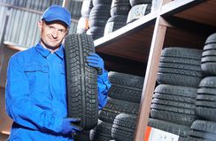 Tyre replacement. mechanic holding tire in store warehouse. Tire sale or replacement. mechanic in blue overalls holding tire in the tyre store warehouse Stock Photos