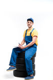 Tyre service worker sitting on a pile of tires. White background, repairman, wheel mounting Stock Photography