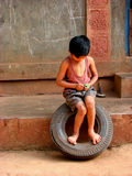 Tyre Toy. A rural boy from Indian village playing on a tyre struggling to open a chocolate wrapper Royalty Free Stock Photo
