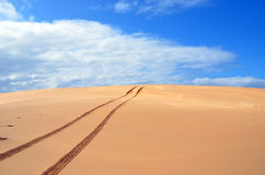 Tyre tracks over sand dunes Stock Photos