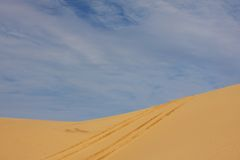 Tyre tracks on sand dune. Under blue sky Stock Images