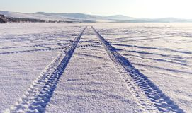 Tyre tracks in the snow on lake Baikal ice surface royalty free stock images