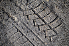 Tyre tread imprint in asphalt. Closeup of tyre tread imprint made in poor asphalt Royalty Free Stock Photo
