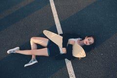 Tyred skater girl sleeping on asphalt in warm summer day Royalty Free Stock Images