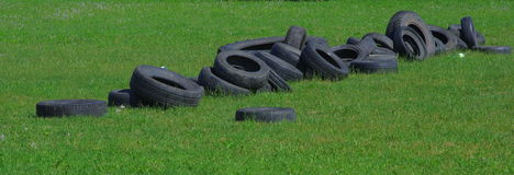 Tyres. Abandoned used tyres on the green grass Royalty Free Stock Photo