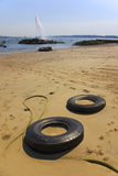 Tyres in the Beach. Two tyres buried in the sand and a geyser in the water Royalty Free Stock Photography