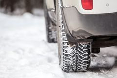 Tyres with ice-gripping tread. Suv car standing on snow at winter. Close up view. Copyspace. Tyres with ice-gripping tread. Suv car standing on snow at winter Stock Photo