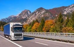 TYROL ÖSTERRIKE - Oktober 14, 2017: En vit blått åker lastbil på en snabb bergväg Royaltyfria Bilder