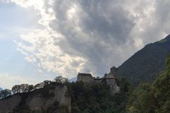 Tyrol Castle, dark storm clouds and mountain panorama in Tirol, South Tyrol. Italy Royalty Free Stock Photography