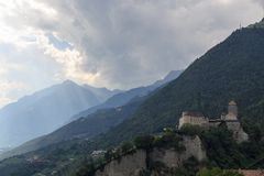 Tyrol Castle, dark storm clouds and mountain panorama in Tirol, South Tyrol. Italy Stock Photography