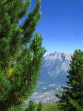 Tyrolean alps. Scenic view of town or city at base of Tyrolean alps with blue sky and green trees in foreground, Austria Stock Images