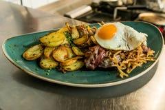 Tyrolean smażyć grule z mięsnym bekonem, pieczarkami i smażącym jajkiem, Obraz Royalty Free