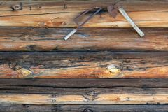 Tyrolian hut exterior wall decorated with axe and saw on strong. Tyrolian shack wall decorated with axe and saw on solid wood planks ageing through wind and royalty free stock images