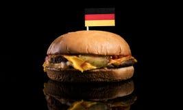 Tysk flagga överst av hamburgaren som isoleras på svart Royaltyfria Foton
