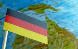 Tysk flagga med en jordklotöversikt som en bakgrund arkivfoto