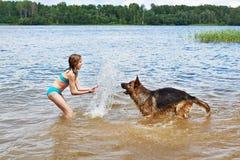 Tysk herde och flicka som spelar i sjön royaltyfri fotografi