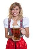 Tysk kvinna i en traditionell bavariandirndl med ölexponeringsglas Royaltyfria Bilder