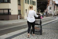 Tysk kvinnapushsittvagn på gatan nära spårvägstation på Sandhausen royaltyfria foton