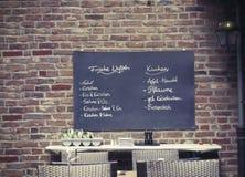 Tysk meny av disk på brädet i kafét utomhus Royaltyfri Foto