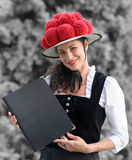 Tysk servitris som rymmer en meny som bär en bollenhut royaltyfria foton