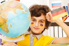 Tysk skolpojke som studerar geografi med ett jordklot Royaltyfri Foto
