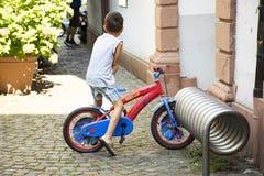 Tyska barn som cyklar den lilla cykeln och stoppar låset, rullar på parkering Royaltyfri Foto