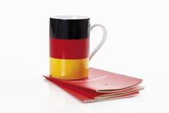Tyska flaggakoppar med bankboken på vit bakgrund arkivfoto