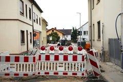 Tyska folkarbetare använder gjort att arbeta för motor för tungt maskineri och bygger vägen i konstruktionsplats royaltyfri foto