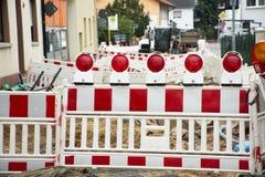 Tyska folkarbetare använder gjort att arbeta för motor för tungt maskineri och bygger vägen i konstruktionsplats royaltyfri bild